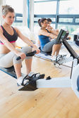 Man and women using the row machines — Stock Photo
