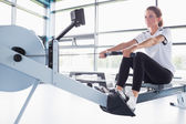Concentrating woman training on row machine — Stock Photo