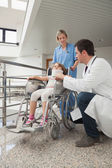 Doctor crouching next to child in wheelchair with nurse pushing — Stock Photo
