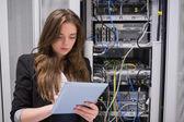 женщина с помощью планшетного пк перед серверами — Стоковое фото