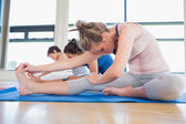 Women in head to knee forward bend pose in yoga class — Stock Photo