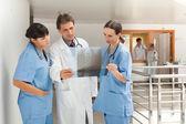 Trois médecins regardant un radiographie du thorax  — Photo