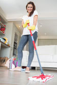 Brunette woman mopping the floor — Stock Photo