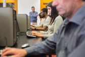 Teacher standing at front of computer class — Stock Photo