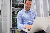 Happy man using laptop to check servers — Photo