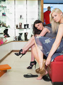 Women trying on shoes in shoe store — Stock Photo