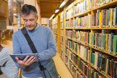 Uomo che tiene un tablet pc in una biblioteca — Foto Stock