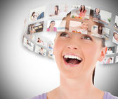 Woman viewing pictures around her head — Stock Photo