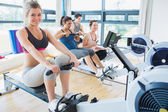 Smiling woman on rowing machine with others — Stock Photo