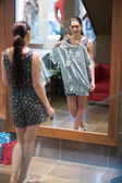 Woman is standing in front of the mirror with clothes — Stock Photo