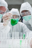 Chemists in protective suits looking at green liquid in beaker — Stock Photo