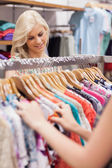 Woman searching at the clothes rack — Stock Photo