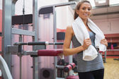 Smiling woman standing beside weight machine — Stock Photo