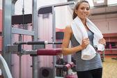 Smiling woman standing beside weight machine — Stock Photo