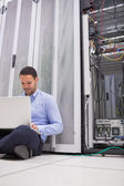 Man working with his laptop on the floor beside servers — Stock Photo