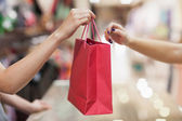 Woman handing over shopping bag — Stockfoto