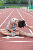Woman stretching on a track — Stock Photo