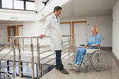 Doctor talks to nurse sitting in wheelchair — Stock Photo
