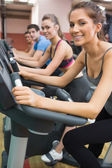 Four enjoying time on exercise bikes — Stock Photo