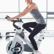 Smiling woman training on exercise bike — Stock Photo