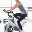 Smiling woman training on exercise bike — Stockfoto