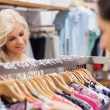 Woman looking at the clothes rack with friend — Stock Photo