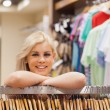 Woman leaning at a clothes rack while smiling — Stock Photo