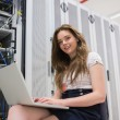 Smiling woman with laptop working with servers — Stock Photo