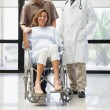 Pregnant woman in wheelchair, partner and doctor smiling — Stock Photo #23050206