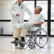 Stock Photo: Doctor talking to min wheelchair