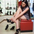 Stock Photo: Woman sitting trying on shoes