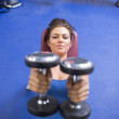Woman straining to lift weights - Stock Photo