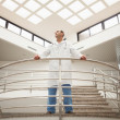 Doctor standing in stairwell looking around — Stock Photo #23050804