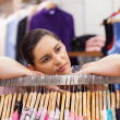 Woman leaning on a clothes rack looking thoughtful - Stok fotoğraf