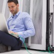 Stock Photo: Mconcentrating on laptop connected to server