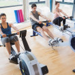 People using rowing machines - Stock Photo