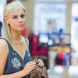 Woman holding handbag at counter — Stock Photo