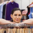 Woman leaning on clothes rack — Stock Photo