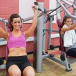 Women using weight machines — Stock Photo