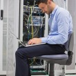 Man on his laptop beside servers — Stock Photo
