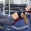 Stock Photo: Woman training with weights while lying