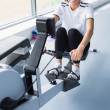 Stock Photo: Happy womon rowing machine