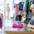 Woman smiling behind counter with folded clothes — Stock Photo #23051506