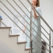 Female patient walking up stairs - Stock Photo