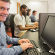 Smiling man sitting in front of the computer - Stock Photo
