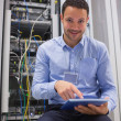 Technician working on tablet pc beside servers — Stock Photo