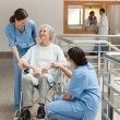 Old woman in wheelchair talking with nurses — Stock Photo #23051874