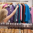Woman searching clothes at the clothes rack — Stock Photo