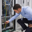 Man plugging a cable into server — Stock Photo