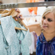 Woman  smiling at clothes — Stock Photo